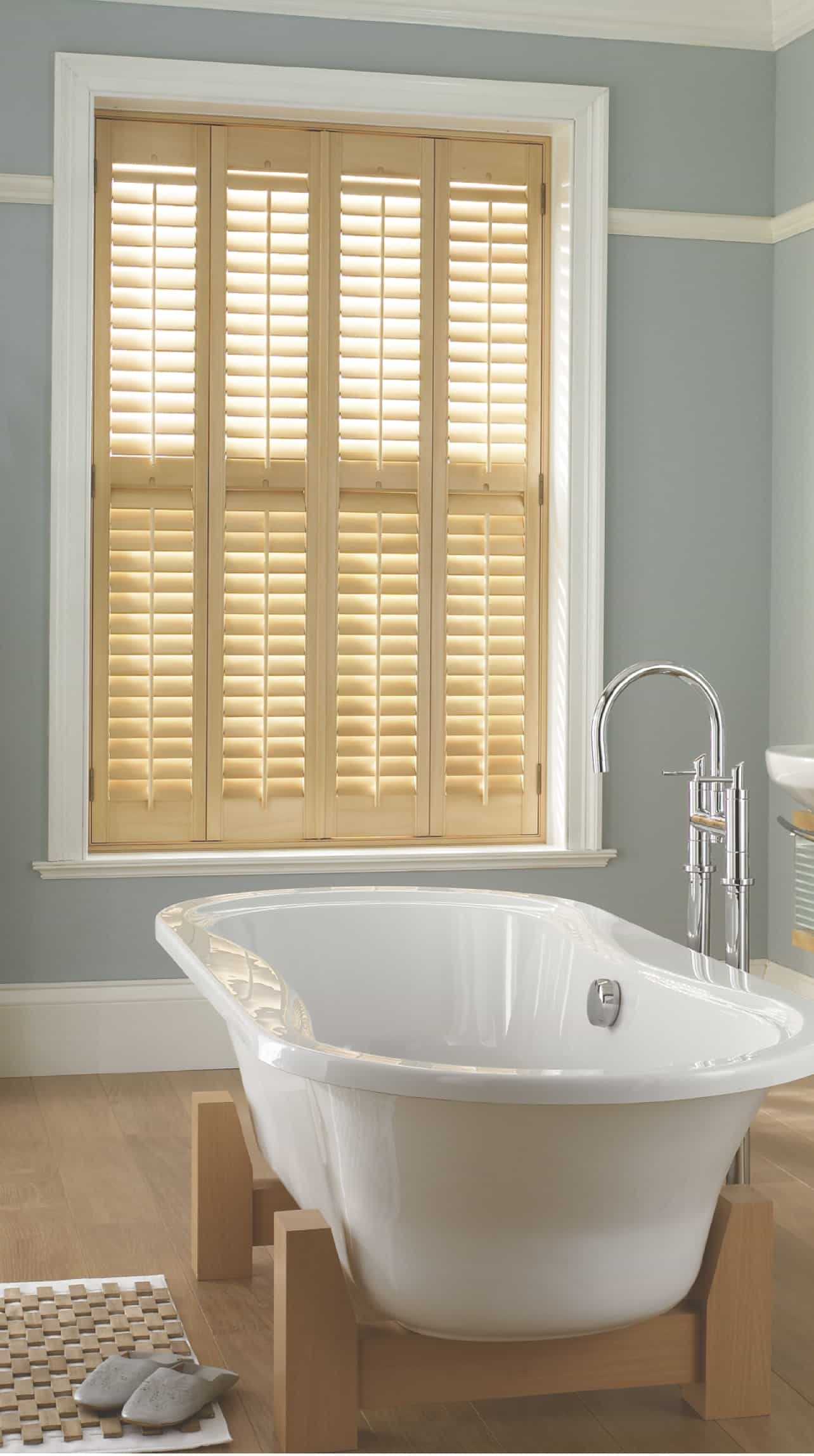 wooden plantation shutter fitted on a large window in a bathroom