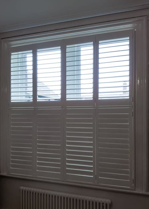 Bedroom plantation shutters in Gosforth done in tier-on-tier style with a white frame