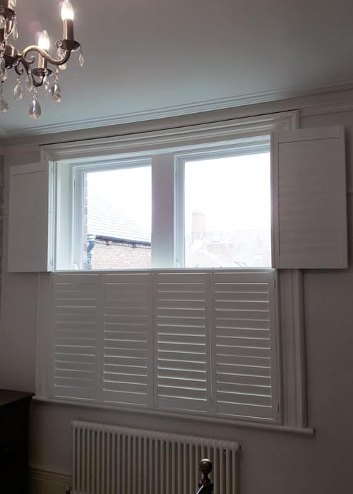 Opened Tier-on-tier window shutters Gosforth installed in bedroom
