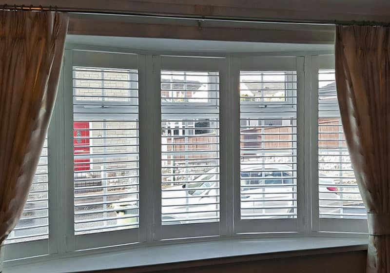 finished installation of white shallow bay window shutters in Jarrow
