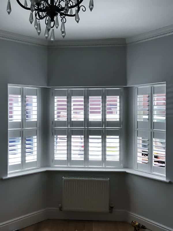 Bi-fold bay shutters with open slats. View from home interior