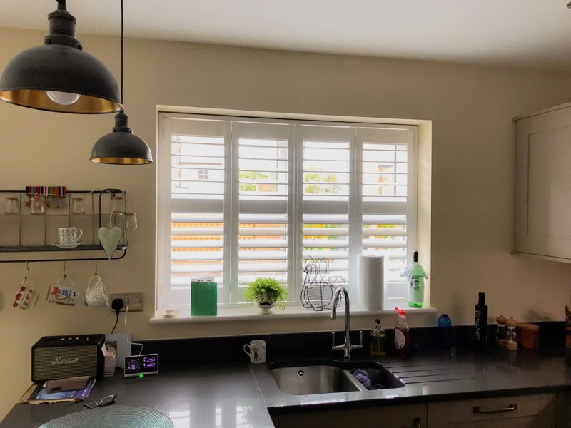 White open plantation shutters in the kitchen, view from inside