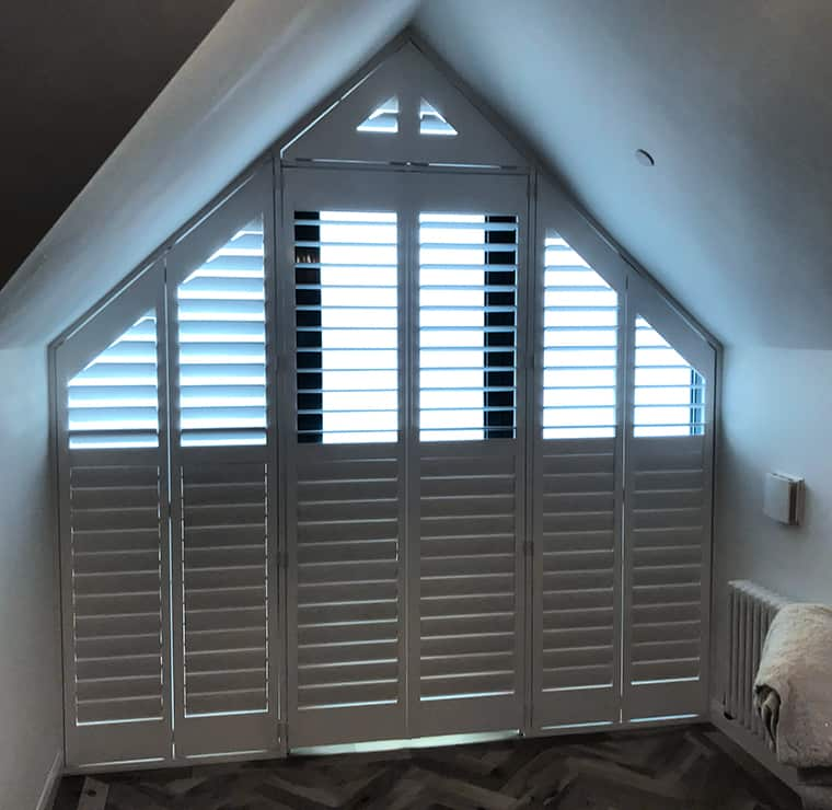 Angled plantation shutters in white, look from inside of a room