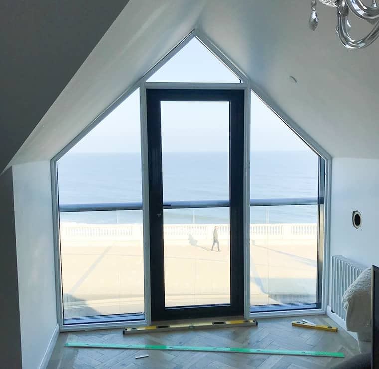Angled window on top of a town house with a view on the sea