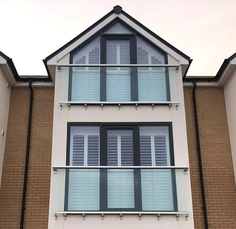 Angled plantation shutters in white, look from the outside of the building